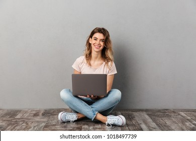 Smiling woman in t-shirt sitting on the floor with laptop computer and looking at the camera over grey background