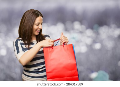 Smiling woman with two shopping bags. Over abstract background