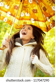 Smiling woman with umbrella in the autumn park