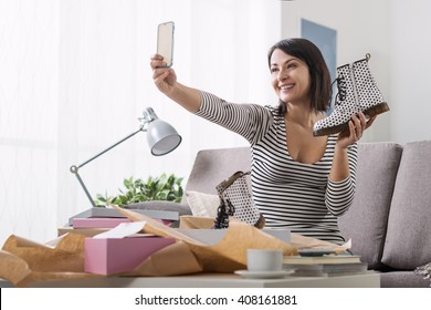 Smiling woman unboxing a postal parcel and taking a selfie with her new purchases using a smartphone