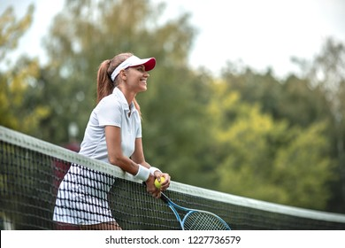 Smiling woman in uniform on the tennis court
