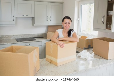 Smiling woman unpacking in kitchen