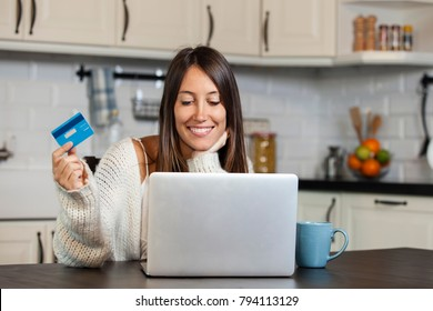 Smiling woman using credit card and laptop for online shopping