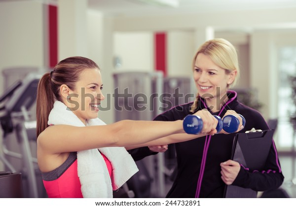 Smiling Woman Using Hand Weights While Personal Trainer Supervises Her Progress
