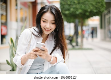Smiling woman using mobile phone on the street