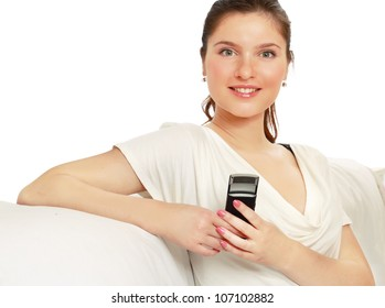 A smiling woman using a mobile phone, sitting on a sofa, over white