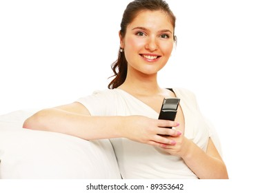A smiling woman using a mobile phone, sitting on a sofa, on white background
