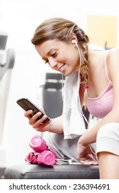 Smiling woman using smart phone with earphones at the gym