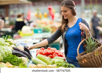 smiling woman with vegetable at market store