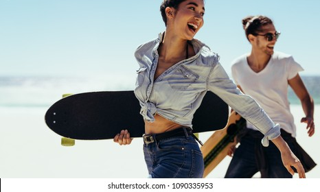 Smiling woman walking with her boyfriend at the beach holding skateboards. Young skaters walking by the beach.
