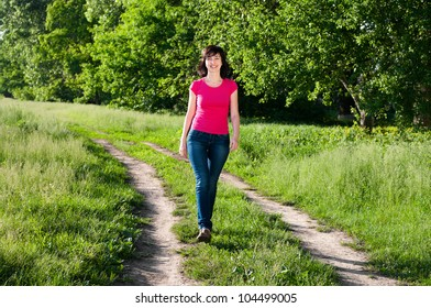 Smiling woman walking outdoors on the forest road in summer