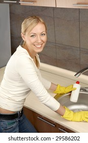 The smiling woman washes a bowl on kitchen