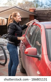 Smiling woman washing car roof with rag