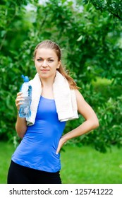 Smiling woman with water bottle after workout
