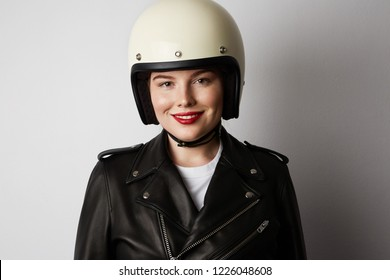 Smiling woman wearing black leather jacket and white moto helmet over background. Fashion, glamour and moto wear concept