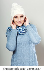 smiling woman wearing a blue woolen sweater and white knitted hat