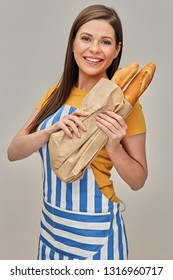 Smiling woman wearing chef apron holding paper bag with baguette bakery. isolated studio portrait.