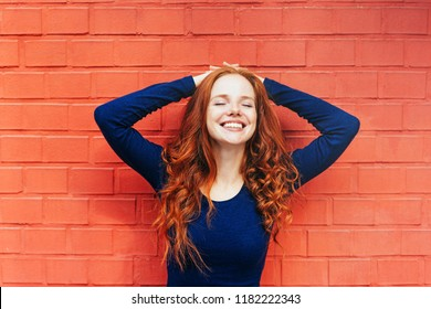 Smiling woman wearing dark blue long sleeved shirt with hands behind her head leaning on red brick wall