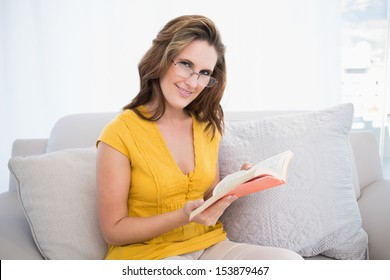 Smiling woman wearing glasses holding book looking at camera