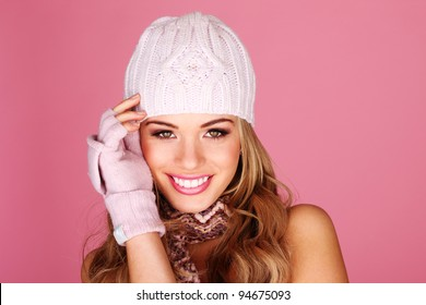 Smiling woman wearing a knitted scarf , mittens and winter cap isolated on pink studio background