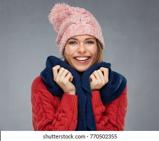 Smiling woman wearing knitted sweater, winter scarf and cup. Isolated portrait.