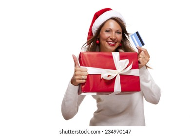 Smiling woman wearing a red Santa hat purchasing Christmas gifts on a bank card holding up a colorful red giftwrapped box with a happy smile and a thumbs up gesture of success, isolated on white