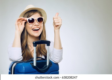 Smiling woman wearing sun glasses and hat with suitcase showing thumb up.