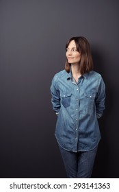 Smiling Woman Wearing Trendy Outfit, Looking to the Left of the Frame While Standing Against Gray Wall Background with Hands on her Back.