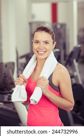 Smiling Woman Wearing Work Out Clothing with Towel Around Neck Standing in Gym