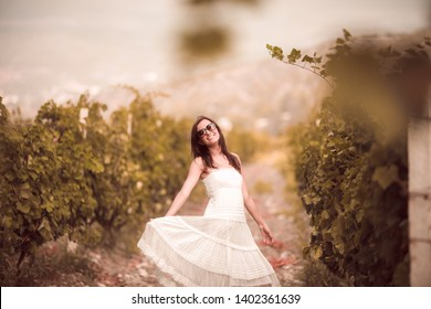 Smiling woman in white dress standing  in vineyard on beautiful crimea background in sunny summer day