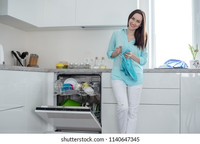 Smiling woman in white jeans and a turquoise shirt with a Cup and a towel in her hands, standing next to an open dishwasher in a white interior kitchen set.