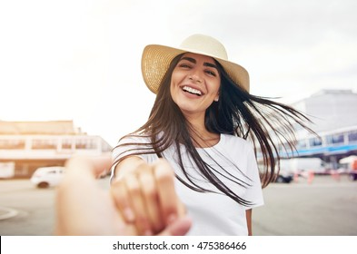 Smiling woman in white shirt stretches hand toward the camera while wearing a straw hat