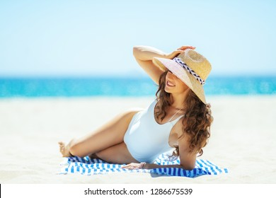 smiling woman in white swimwear on the ocean shore looking into the distance while laying on a striped towel. woman wearing straw hat. Covering up with a hat to avoiding the harsh summer midday.