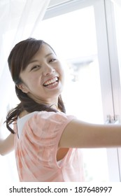smiling woman who opens curtain