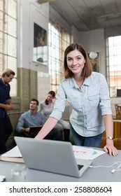 Smiling woman working in a design studio standing at her desk with a laptop and large paper drawing while her colleagues work in the background