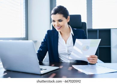 Smiling woman working at her desk using notes and laptop