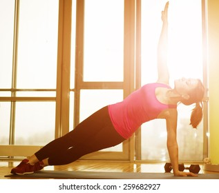smiling woman working out at home against sunny background