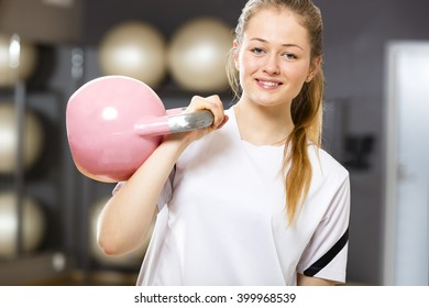 Smiling woman in workout outfit holds kettlebell at fitness gym