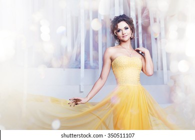 smiling woman in yellow evening dress and with beautiful hairstyle, party
