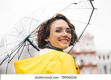 Smiling woman in yellow raincoat and glasses taking pleasure in walking through city under big transparent umbrella, during cold rainy day