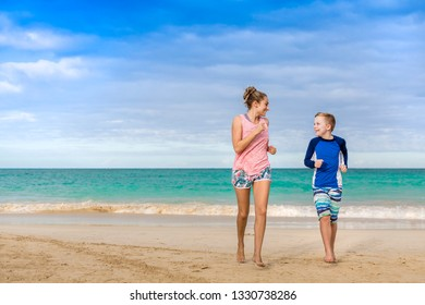 Smiling women and boy running together on a beautiful beach on vacation. Idyllic photo of a family beach holiday. Happy candid people in a scenic setting