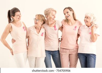 Smiling women of five generations with pink ribbons embracing each other, breast cancer concept