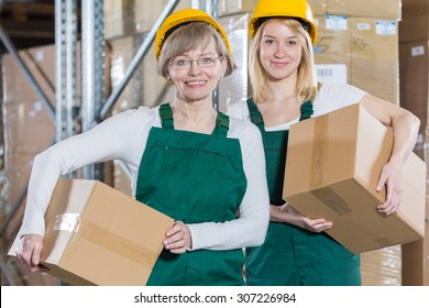 Smiling women are holding packages ready for transport