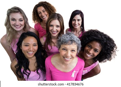 Smiling women in pink outfits posing for breast cancer awareness on white background