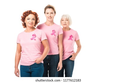 smiling women with pink ribbons standing together and looking at camera isolated on white, breast cancer awareness concept