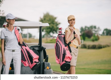 smiling women in polos and caps with golf equipment at golf course on summer day