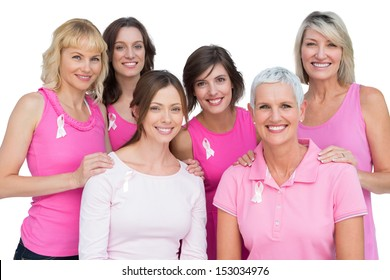 Smiling women posing and wearing pink for breast cancer on white background
