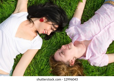 smiling women rest on the green grass