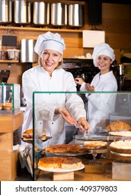 Smiling women selling tarts and sweet pastry in coffee-house