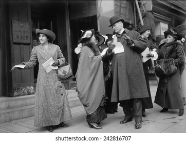 Smiling women suffragists hand out literature to advertise the 1913 parade in New York City.